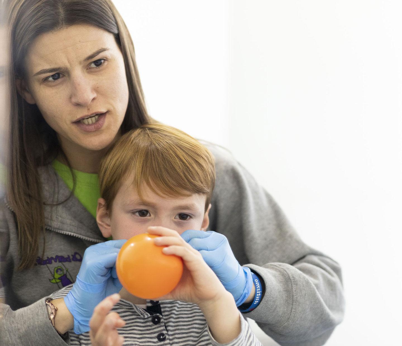 niño con terapeuta soplando globo naranja