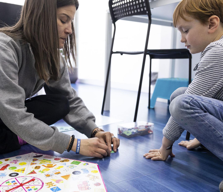 profesora jugando con alumno en el suelo