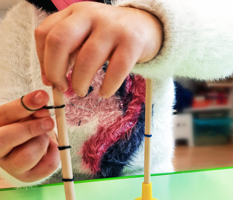manos de una niña anudando unas gomas negras en unos palos verticales