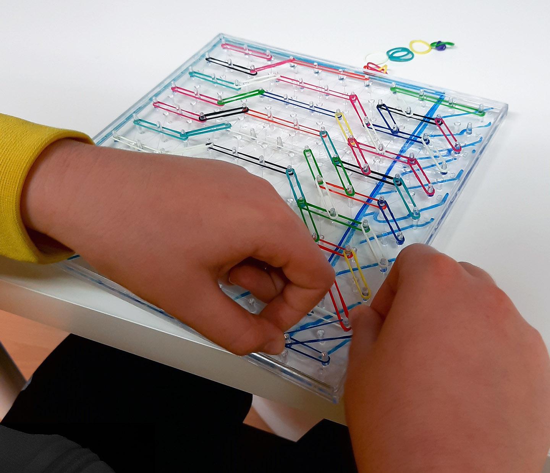 manos de una niña haciendo un ejercicio de insertando gomas de colores en un tablero